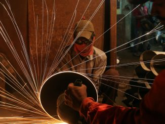 A worker cuts metal inside a workshop manufacturing metal pipes in Mumbai