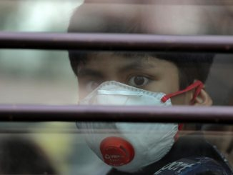 A schoolboy wearing a protective mask looks on from the inside of a school bus at Silver Line Prestige School in Ghaziabad